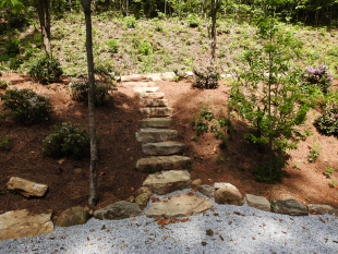 Stone steps and landscaped hill by Gonzalez Landscaping and Home Improvement