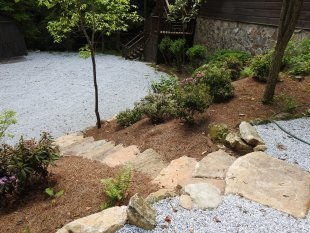 View from the top of stone steps to parking area by Gonzalez Landscaping and Home Improvement