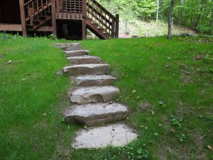 Stone steps down to the fire pit area by Gonzalez Landscaping and Home Improvement